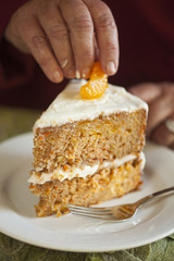 slice of mandarin orange being placed on Carrot Cake