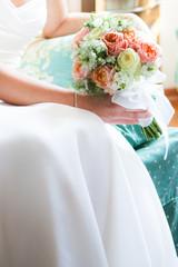 Sposa seduta con bouquet in mano