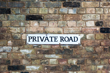 Private road sign warning of trespassing on a wall