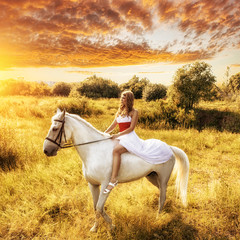 woman on horse over sunset