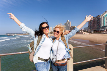 cheerful tourists by beachfront