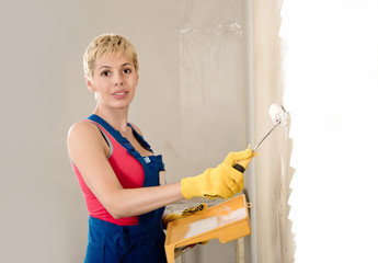 young beautiful woman paints the wall, the construction work