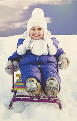 Adorable little girl on a sled at winter sunny day