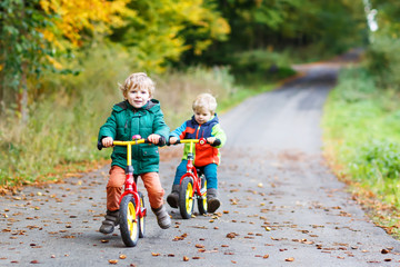 Two active brother boys having fun on bikes in autumn forest