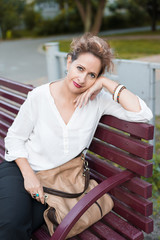 relaxed smiling woman in a park bench