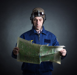 Portrait of a pilot with a geographical map in hand.