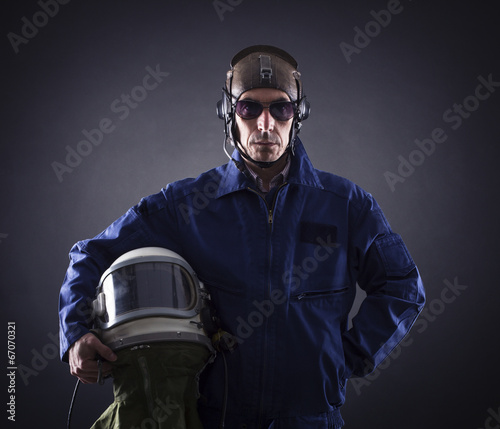 Pilot in military uniform on a black background. - 67070321
