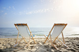 couple of chairs on sandy beach at sunset - relaxation concept