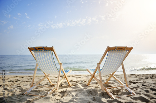 Keuken foto achterwand Zee / Oceaan couple of chairs on sandy beach at sunset - relaxation concept