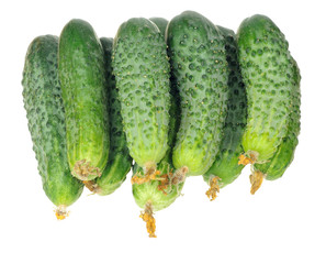 stack of cucumbers with dry flowers isolated over white