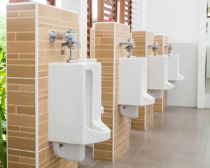 White urinals with ceramic tile on wall.