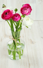 ranunculus flowers in a glass vase on wooden table