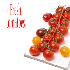 colorful cherry tomatoes on a white wooden board, isolated