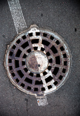 Manhole with metal cover in asphalt with white road marking line