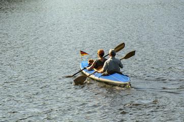 Mann, Frau und Hund von hinten im Ruderboot bei Gegenlicht