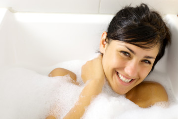 Happy girl having fun in bathtub smiling