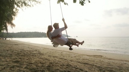 Young couple on swing at beach-Honeymoon