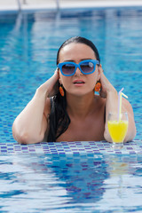 Woman  in swimming pool with orange juice. Vacation  concept
