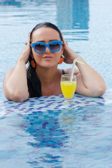 Pretty woman in swimming pool with orange juice.