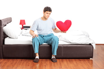 Sad guy sitting alone on bed and holding a heart