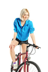 Young blond female posing on a bicycle