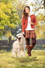 Beautiful girl walking her dog in park