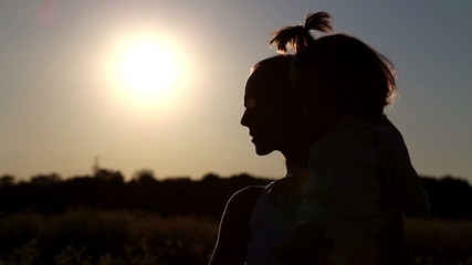 Young mother holding  baby in her arms at sunset.