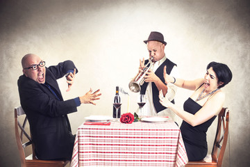 couple disturbed by a trumpet musician while having dinner