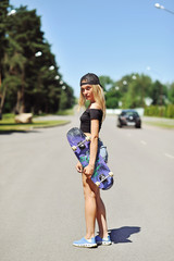 Beautiful young woman holding a skateboard