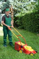 Gärtner mäht Rasen mit Rasenmäher