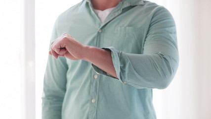 man unbuttoning his sleeve at home