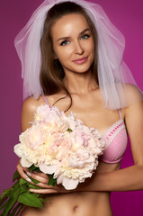 Beautiful bride in veil and lingerie with bouquet of peonies