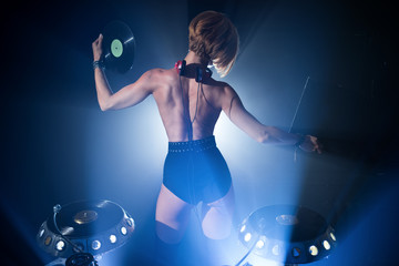 Girl in a nightclub DJ plays on the plates