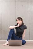 床に座ってラップトップを使う女性