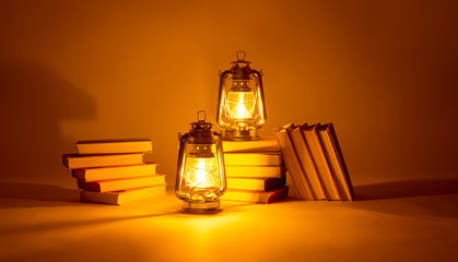 Burning kerosene lamps and books, concept magic of light