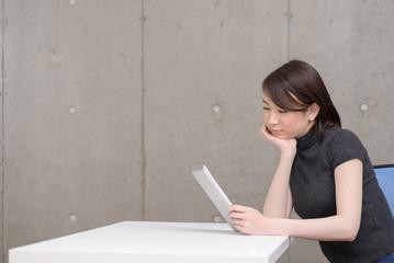 タブレット端末を使う若い女性