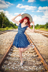 Beautiful woman with blue dress and hat.