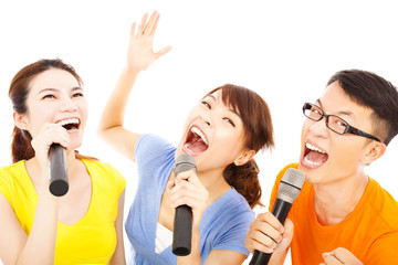 happy asian young group having fun singing with microphone
