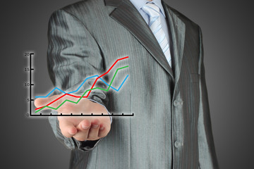 Business man holding a financial graph on grey background.