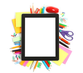 Tablet PC with school office supplies on white background .