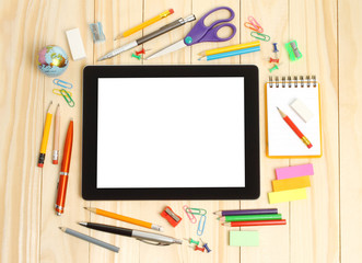 Tablet PC with school office supplies on wooden background .