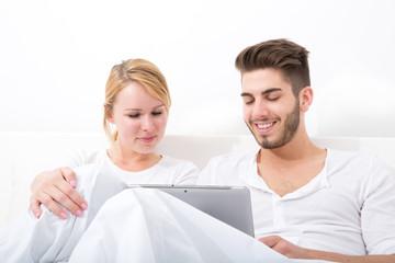 Glückliches Pärchen mit Tablet Pc im Bett