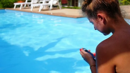 Young Woman Texting on the Phone while Relaxing in Private Pool