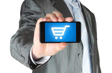 Man holds smart phone with shopping cart on white background.