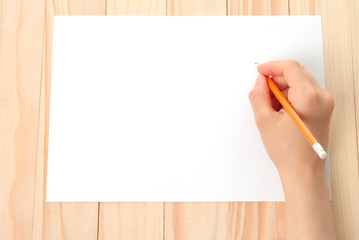 Woman hand with pencil and paper on wooden background .