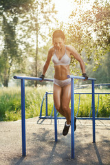 fitness woman doing exercise on parallel bars sunny outdoor