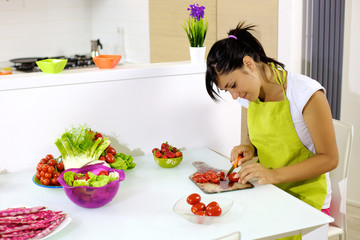Cute young woman at home preparing salad