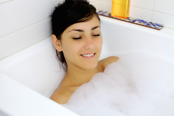 Young woman relaxing taking a bath