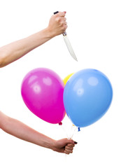 Female Hand Bursting Colorful Balloons with Knife. White Backgro