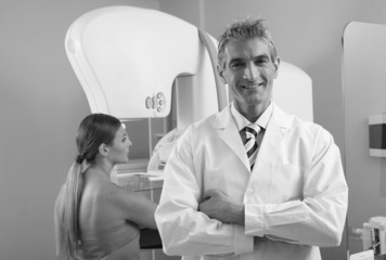 Smiling male doctor with woman in 40s undergoing mammography sca